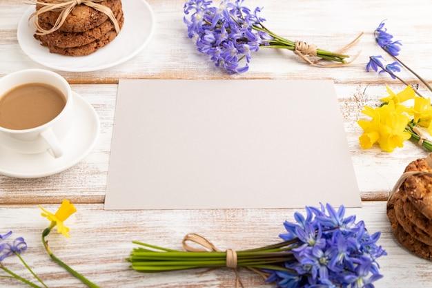 Grijs papier met havermoutkoekjes, lente sneeuwklokje bloemen boshyacinten, narcissen en kopje koffie
