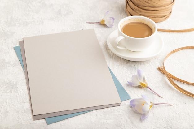 Grijs papieren bladmodel met krokusbloemen en kopje koffie op grijze betonnen ondergrond.