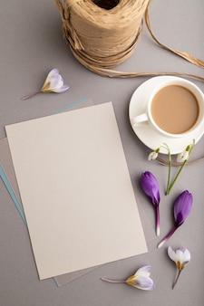 Grijs papieren vel mockup met krokus en galanthus bloemen en kopje koffie