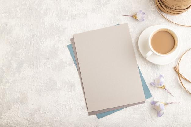 Grijs papieren vel mockup met lente sneeuwklokje krokus bloemen en kopje koffie