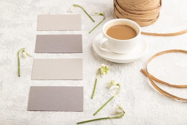 Grijs papieren visitekaartje mockup met lente galanthus bloemen en kopje koffie