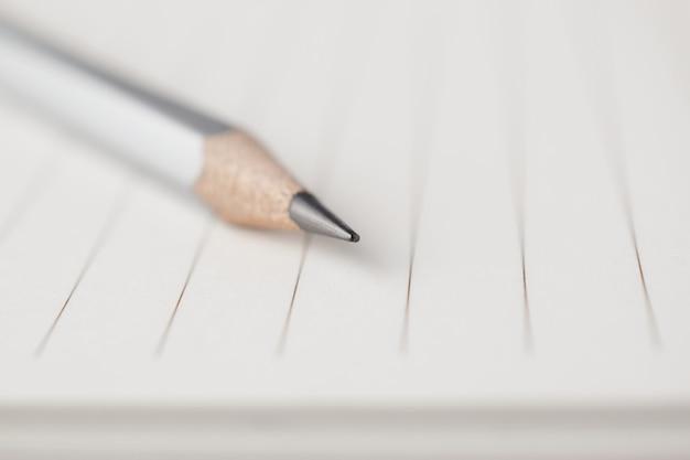 Grijs potlood wijst naar het lege gebied van notaboek