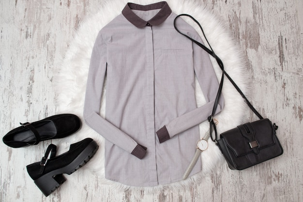Grijs shirt, zwarte schoenen en handtas