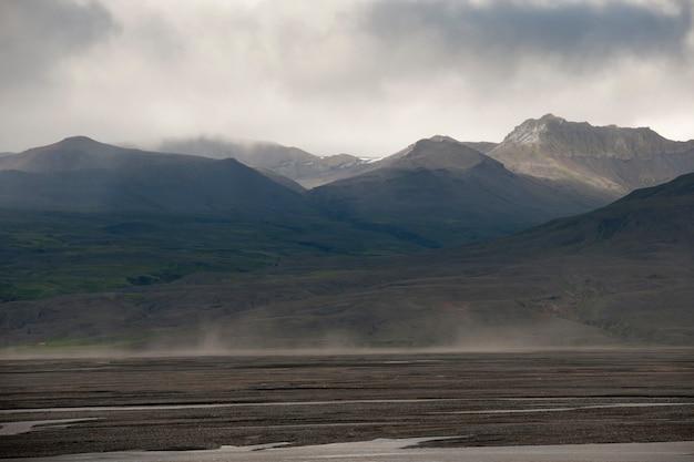 Grijs wolkenlandschap van bergketen en weide
