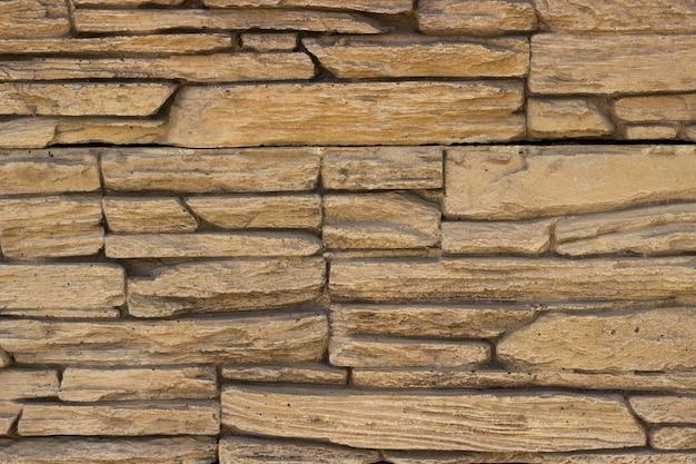 Grijsbruine ongelijke bakstenen muur