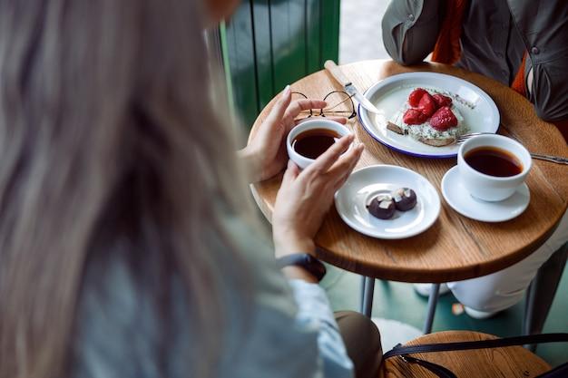 Grijsharige dame neemt een kopje koffie en brengt tijd door met een vriend in een gezellig café