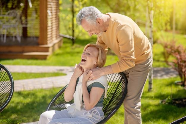 Grijsharige glimlachende blanke man leunend over zijn opgewekte blonde vrouwelijke echtgenoot zittend in de leunstoel