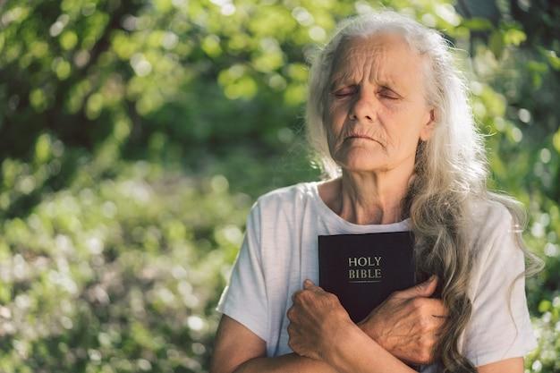 Grijsharige grootmoeder houdt bijbel in haar handen.