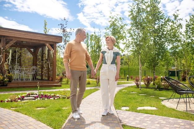 . grijsharige man en een lachende blonde vrouw hand in hand buitenshuis
