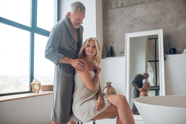 Grijsharige man in badjas die zich dichtbij blonde vrouw in een handdoek bevindt