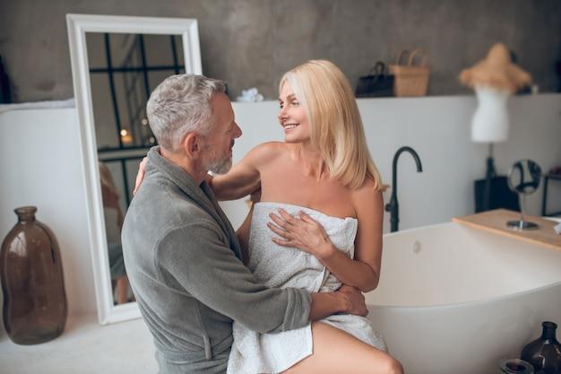 Grijsharige man in badjas en blonde vrouw in handdoek romantisch gevoel