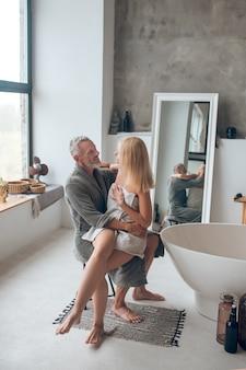 Grijsharige man in badjas knuffelen een blonde vrouw op zijn knieën