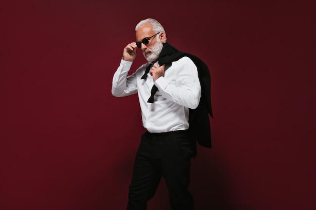 Grijsharige man in zwarte broek en wit overhemd houdt jas vast