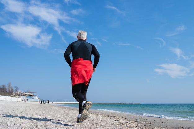 Grijsharige man loopt op het strand