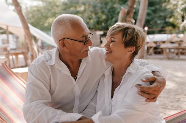 Grijsharige man met bril in shirt met lange mouwen knuffelen en kijken naar kortharige lachende vrouw in witte blouse op strand.