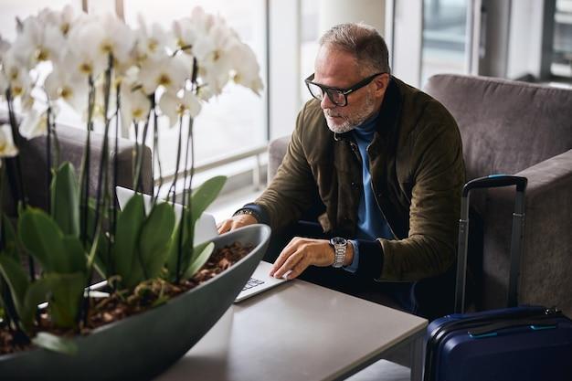 Grijsharige man staart naar zijn laptopscherm
