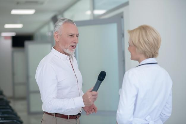 Grijsharige mannelijke journalist die blonde vrouwelijke arts in gang interviewt