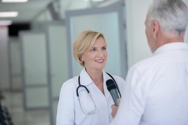 Grijsharige mannelijke journalist die glimlachende blonde vrouwelijke arts in gang interviewt