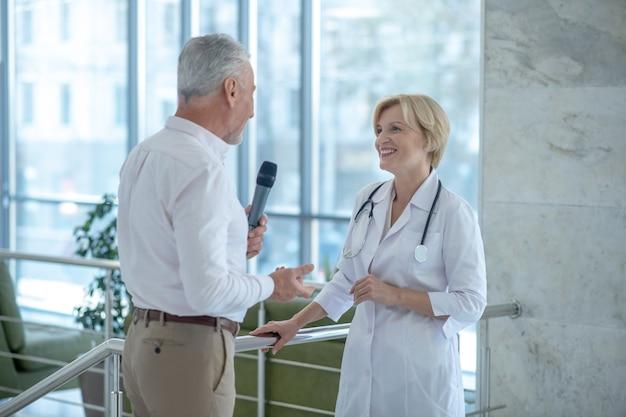 Grijsharige mannelijke journalist die glimlachende blonde vrouwelijke arts interviewt