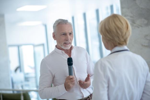 Grijsharige mannelijke journalist die microfoon houdt, blonde vrouwelijke arts interviewt