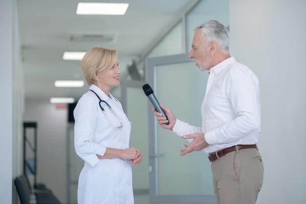 Grijsharige mannelijke journalist met interview met lachende blonde vrouwelijke arts in gang