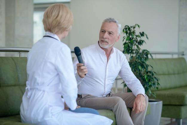 Grijsharige mannelijke journalist met microfoon, zittend op de bank, blonde vrouwelijke arts interviewen