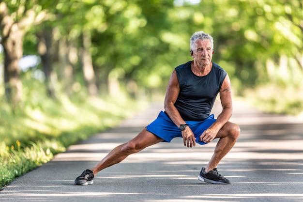 Grijsharige oude man die nog steeds in vorm is, rekt zijn benen tijdens zijn pre-workout warming-up.