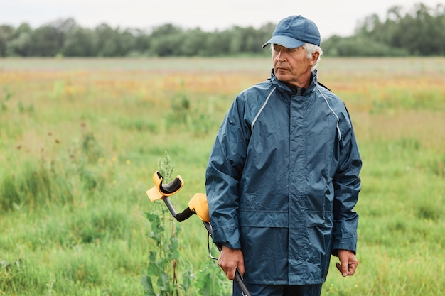 Grijsharige volwassen man die buiten poseert, metaaldetector in handen houdt, in het veld wegkijkt met peinzende uitdrukking