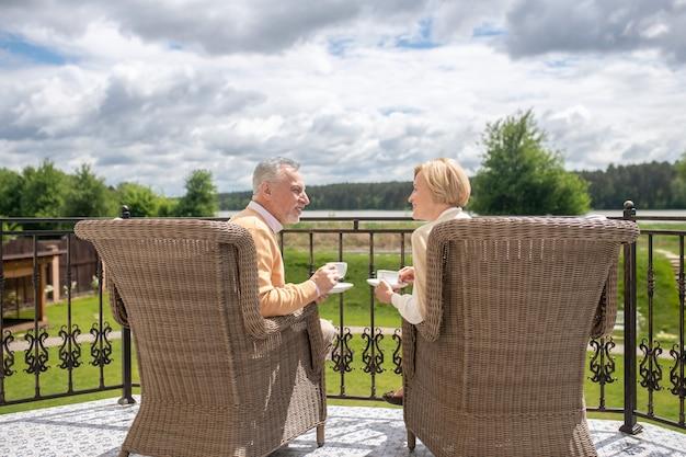 Grijsharige volwassen man en een lachende blonde dame zittend in de rieten fauteuils met kopjes en schotels in hun handen