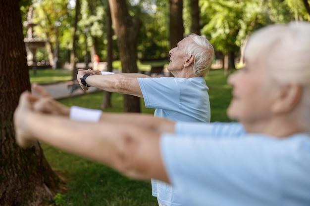 Grijsharige volwassen man traint met vrouw op weide in stadspark