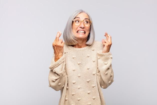 Grijsharige vrouw die angstig haar vingers kruist en met een bezorgde blik hoopt op geluk