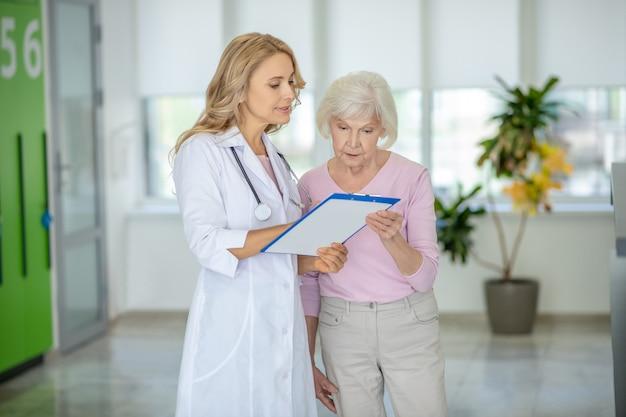 Grijsharige vrouw in gesprek met de dokter over haar onderzoeksresultaten