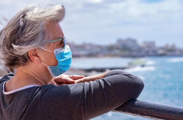 Grijsharige vrouw met chirurgisch masker kijkend naar zeegezicht en horizon over water