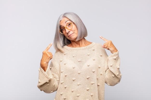 Grijsharige vrouw met een slechte houding die trots en agressief kijkt, naar boven wijst of een grappig teken maakt met de handen
