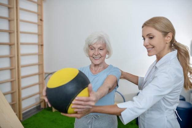 Grijsharige vrouw trainen met een bal in een revalidatiecentrum