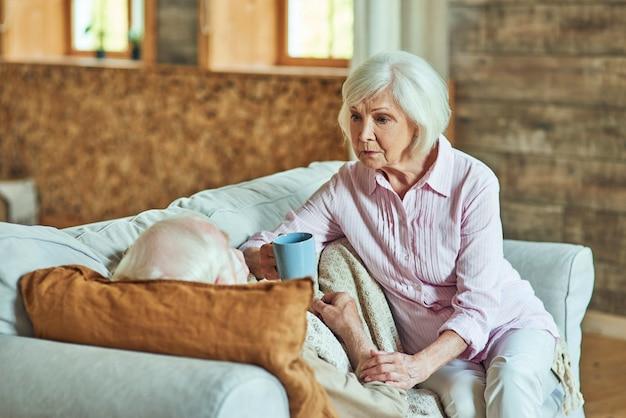 Grijsharige vrouw zorgt thuis voor zieke echtgenoot
