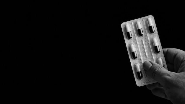 Grijsschaal die van een persoon is ontsproten die een pak capsules met een zwarte houdt