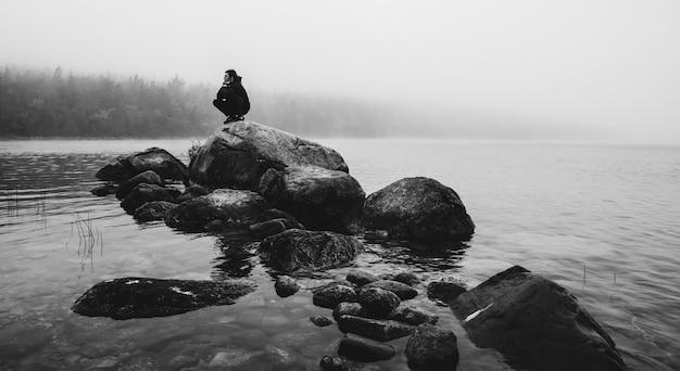 Grijsschaal die van een persoon is ontsproten die op grote rots in het midden van mistige rivier zit