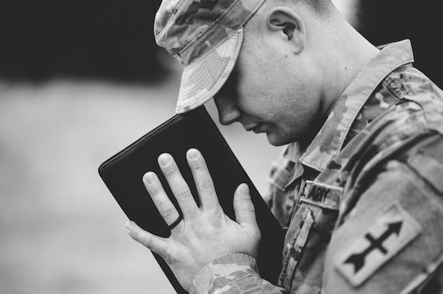 Grijsschaal van een jonge soldaat die bidt terwijl hij de bijbel vasthoudt