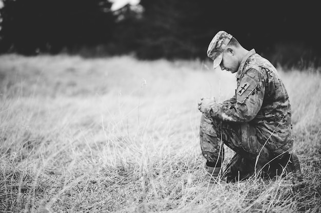 Grijsschaal van een jonge soldaat die bidt terwijl hij op een droog gras knielt