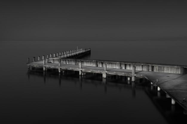 Grijstinten shot van een houten pier in de buurt van de zee overdag
