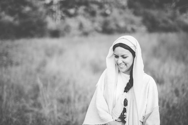 Grijstinten shot van een vrouw die een bijbels gewaad draagt en lacht