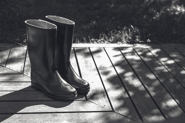 Grijstinten shot van laarzen op een houten oppervlak