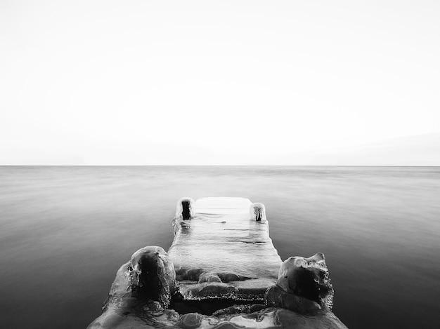 Grijstinten van een brug bedekt met het ijs op de zee onder het zonlicht