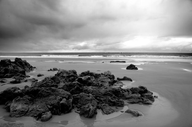 Grijstinten van het strand omgeven door rotsen en een golvende zee onder een bewolkte hemel overdag
