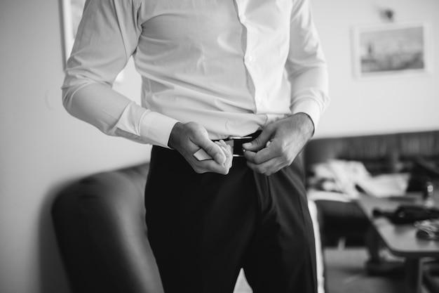 Grijswaardenclose-up van een zijn riem aanspannen en zakenman die klaar voor een belangrijke vergadering worden