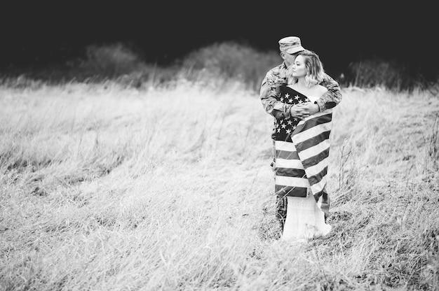 Grijswaardenfoto van een amerikaanse soldaat die zijn vrouw knuffelt terwijl ze omwikkeld is met een amerikaanse vlag