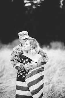 Grijswaardenfoto van een amerikaanse soldaat die zijn vrouw knuffelt