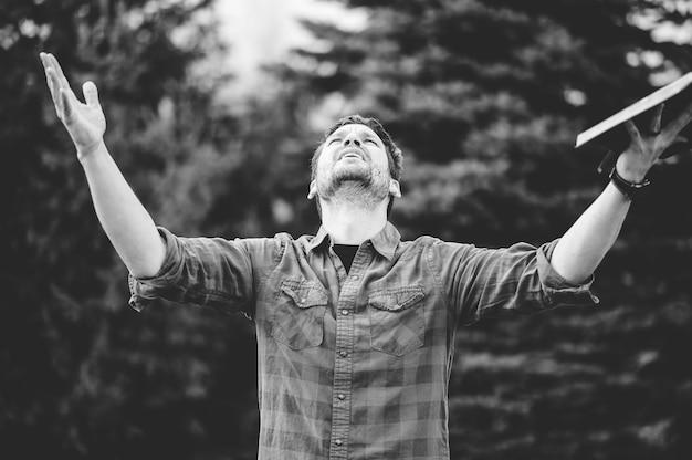 Grijswaardenfoto van een jonge man die met open armen omhoog kijkt