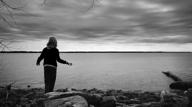 Grijswaardenfoto van een kind dat op de rotsen bij de zee staat en geniet van de prachtige, rustige horizon
